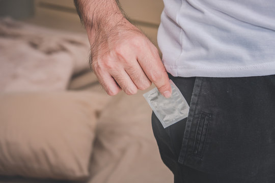 Midsection Of Man Removing Condom From Pocket While Standing At Home