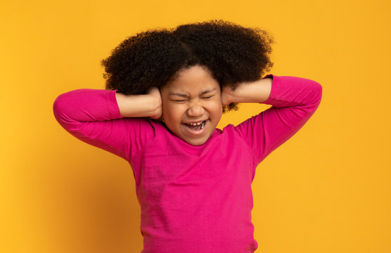 Portrait of annoyed little african girl covering ears with hands
