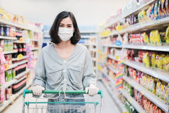 Asian woman wearing face mask and rubber glove push shopping cart in suppermarket departmentstore. Girl choosing, looking grocery things to buy at shelf during coronavirus crisis or covid19 outbreak.