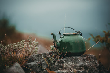 Keuken foto achterwand Schip An old green kettle stands on a stone on top of a mountain. A teapot thrown in the forest.