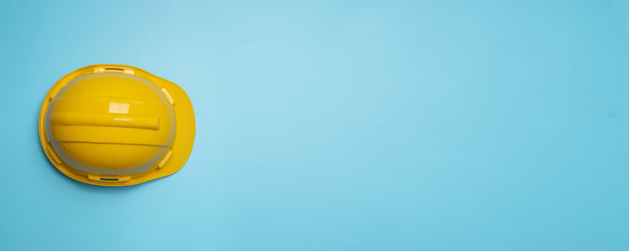 Yellow construction and protection helmet on blue background