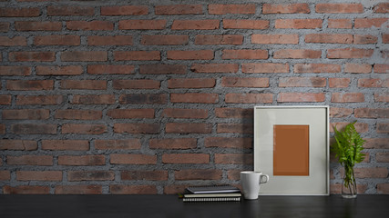 Photo of black working desk along with book, notebook, picture frame, potted plant and coffee cup putting together on it with brick wall as background. Orderly workspace concept.