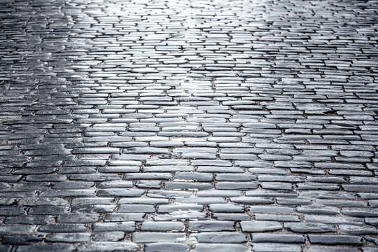 old wet stone paved road after rain. low angle view