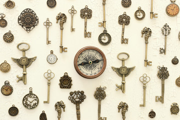 Image of old antique keys and compass over wooden background. Top view, flat lay