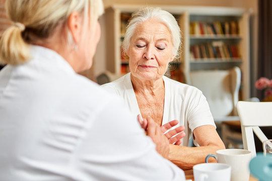 Frau vom Pflegedienst tröstet Seniorin im Altenheim