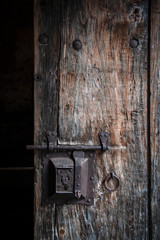 Ancient rusty steel lock bolt with a key hole installed on an old wooden door from medieval age