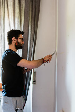Doing homework. Adult man repairing holes on a wall with putty