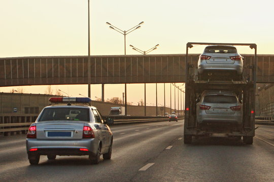 Two-level russian car carrier rides on the highway in front of a police car in the evening against background of a pedestrian bridge, large-size road transport with a height restriction of the cargo