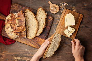 Woman hands cut fresh organic artisan bread. Healthy eating, buy local, homemade bread recipes concept. Top view, flat lay
