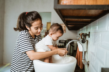 mother help her baby to wash hand in the sink