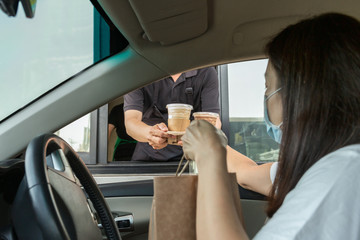 Woman in protective mask taking coffee at drive thru during covid-19 outbreak.