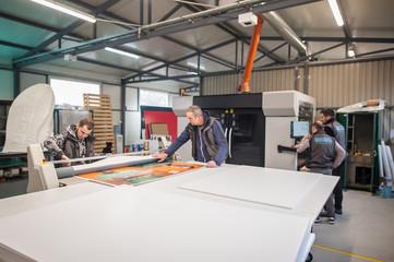 Large group of technicians works in printing printshop press hall Fotomurales