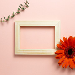 Fotorolgordijn Gerbera Empty photo frame with orange gerbera daisy flower and eucalyptus leaf on pink background. Floral composition, flat lay, top view, copy space
