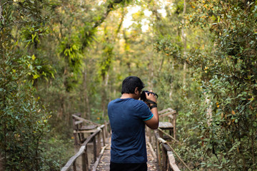 Photographer Taking a Photo from Wooden Walkway inside forest