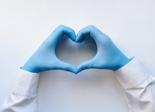 Hands of a doctor or nurse in medical gloves depict a heart on a white background, caring doctor and medicine concept.