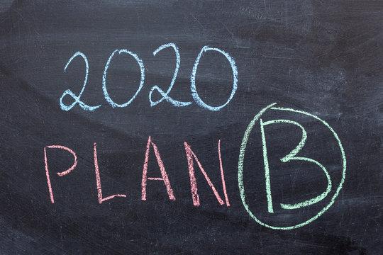 """2020 Plan B"" handwritten with white chalk on a blackboard"