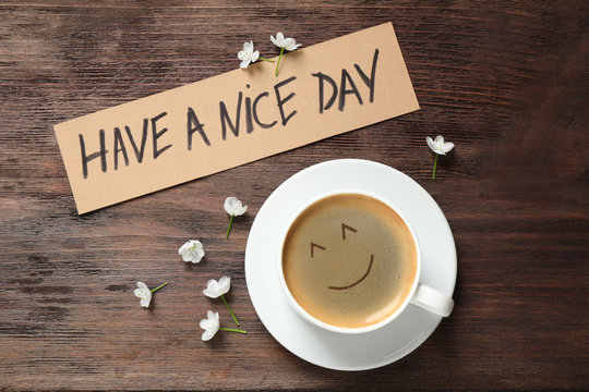 Delicious coffee, flowers and card with HAVE A NICE DAY wish on wooden table, flat lay. Good morning