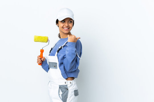 Painter woman over isolated white background pointing to the side to present a product