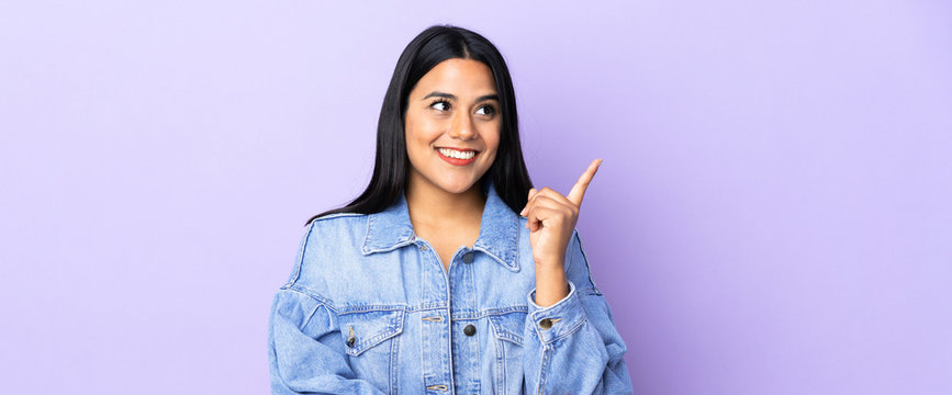 Young latin woman woman over isolated background pointing up a great idea