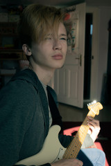 Teenage boy is dreaming about a new song. In his room he is playing around on the  guitar.