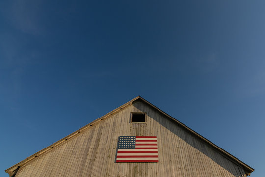 Old wooden barn with american flag.