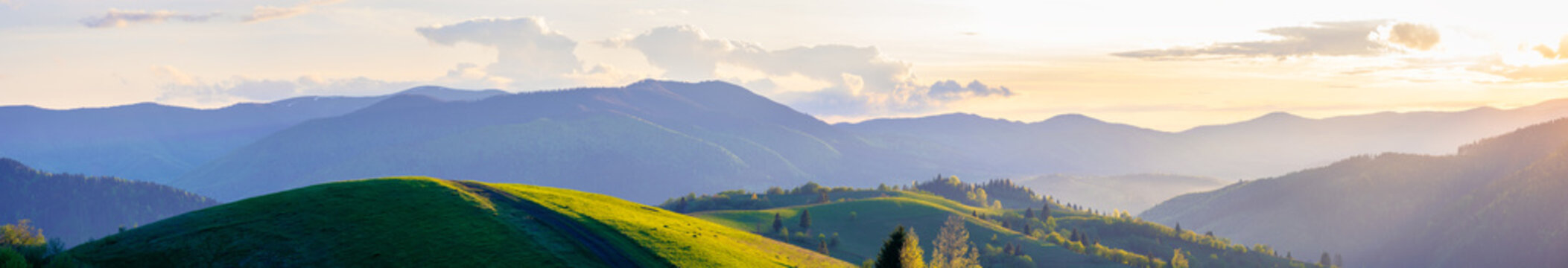 panorama of mountainous countryside in springtime at dusk. path through rolling hills. ridge in the distance. clouds on the sky. beautiful rural landscape of carpathians
