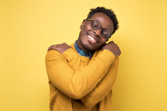 Pleased african american man in yellow clothes and glasses hugs himself, has high self esteem. Studio shot on colored wall.