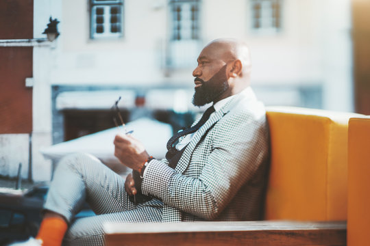 True tilt-shift portrait of a dashing mature bald African man with a neat beard, in a checkered fashionable costume and orange socks, sitting outdoors on a sofa, sunny day, selective focus on the face