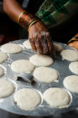 Hand of ethnic woman preparing Indian Idly