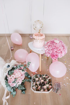 Pastel birthday cake, balloons and flowers
