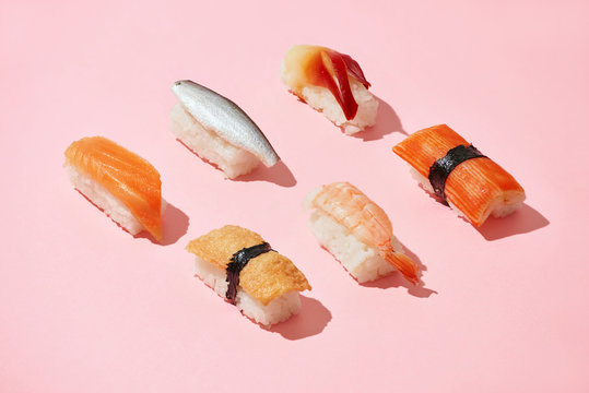 Sushi set of different nigiri idea, creative top on a pink background isolated