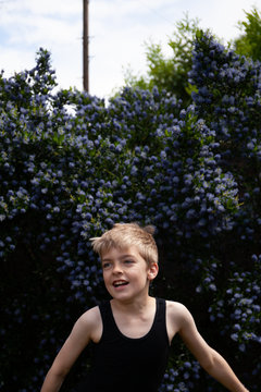 Boy dancing in front of a lilac bush.