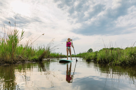 Young Girl On Stand Up Paddle Board Exploring Chesapeake Bay