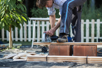 Man using saw to cut wooden planks Wall mural