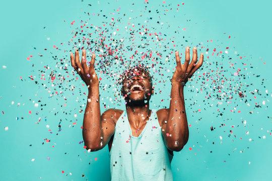 Cheerful black ethnic man throwing confetti on air.