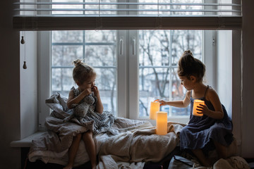 Little girls playing on a window with candles at home in the evening
