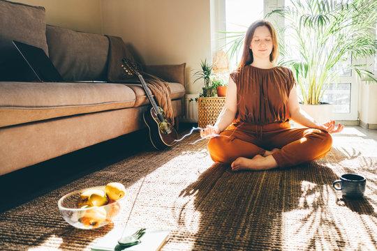 Woman doing yoga at sunny home.
