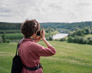 Young woman in burgundy dress with black bag taking picture on her camera