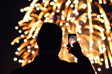 Man photographing fireworks using smartphone