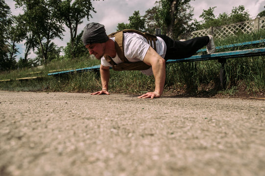 powerful street work-out of the crossfit athlete - doing push-ups in the playground