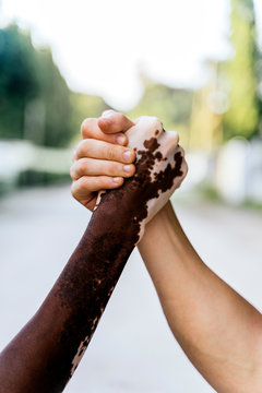 Two diverse people holding hands in first position.