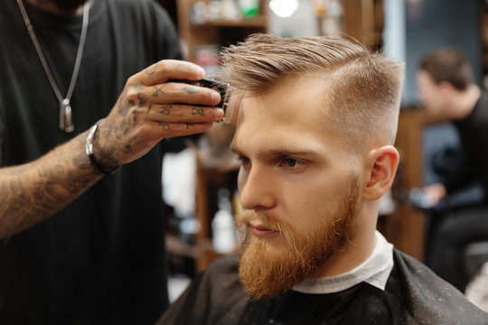 Crop barber trimming hair of bearded man