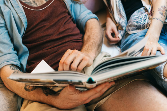 Anonymous Caucasian Couple Looking at Picture Book in Bed