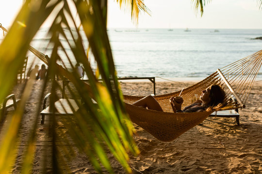 Woman relaxing on the hammock on the beach at sunset
