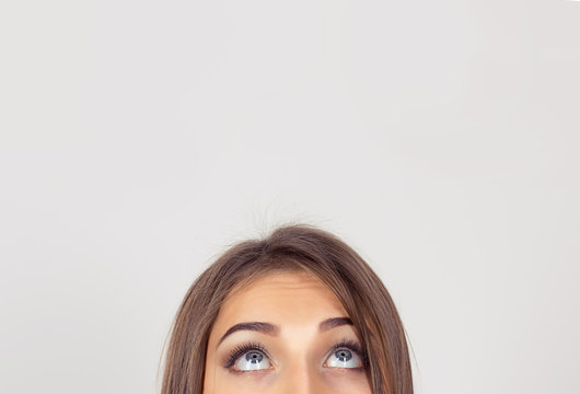 cropped image half face eyes of woman looking up white grey wall