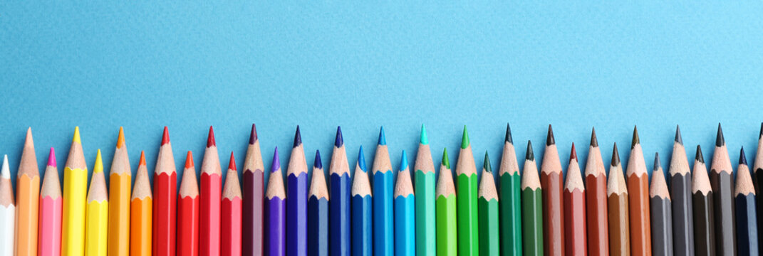 Color pencils on light blue  background, flat lay with space for text. Banner design