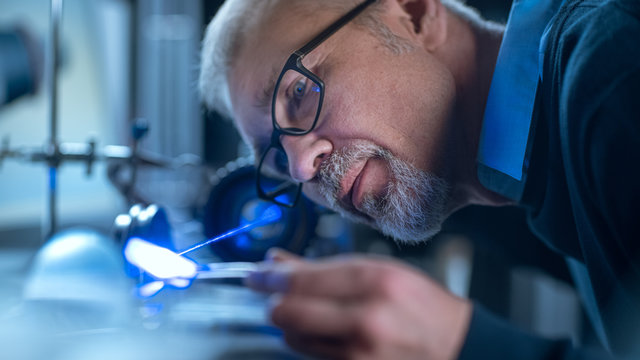 Close-up Portrait of Focused Middle Aged Engineer in Glasses Working with High Precision Laser Equipment, Using Lenses and Testing Optics for Accuracy Required Electronics