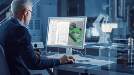 Engineer Works on Computer Uses CAD Software to Design 3D Industrial Machinery Component. In the Background Robot Arm Concept Standing in Heavy Industry Engineering Facility. Over the Shoulder Shot