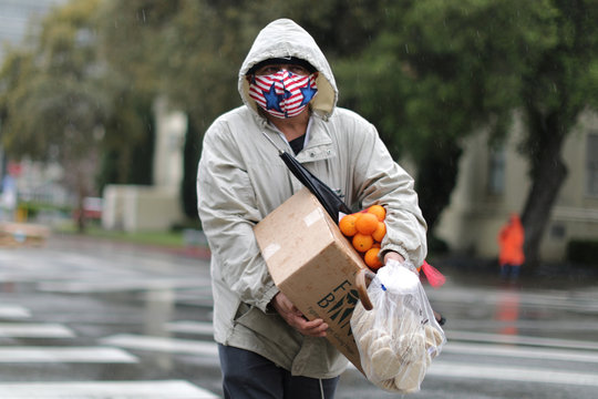 A man carries fresh food in the rain at a Los Angeles Regional Food Bank giveaway of 2,000 boxes of groceries, as the spread of the coronavirus disease (COVID-19) continues, in Los Angeles