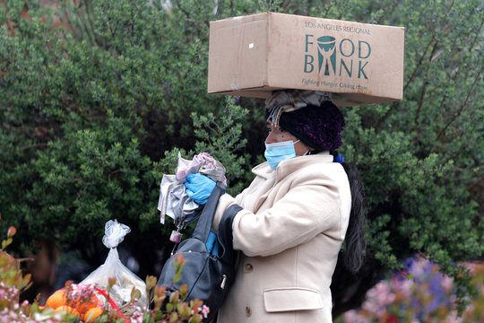 A woman carries fresh food in the rain at a Los Angeles Regional Food Bank giveaway of 2,000 boxes of groceries, as the spread of the coronavirus disease (COVID-19) continues, in Los Angeles